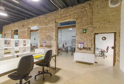 Plataforma empresarial con espacio para eventos, sala abierta de coworking y despachos privados
