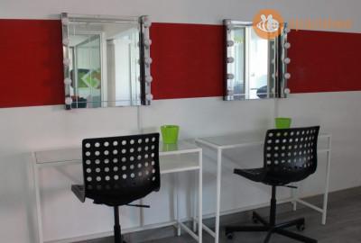 Sala amplia y de diseño preparada para maquillaje, peluquería y vestuario.